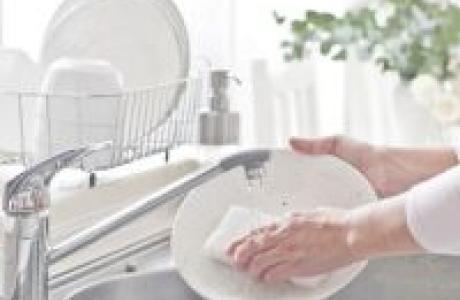 Γυναίκα που πλένει πιάτα σε καθαρό νεροχύτη